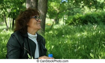 woman sitting on grass and smiling. Family holiday in the park