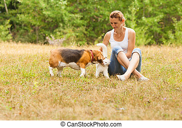 Woman sitting on grass looking at her pets playing