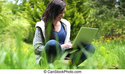 Woman sitting on grass using her la