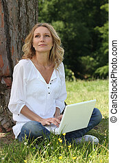 Woman sitting on grass with a computer