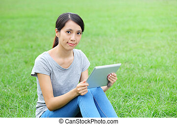 Woman sitting on grass with tablet computer