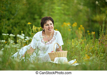 woman sitting on grass with wicker basket