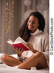 Woman sitting on her bed and smiling while reading a book