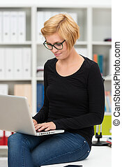 Woman sitting on her desk working on a laptop