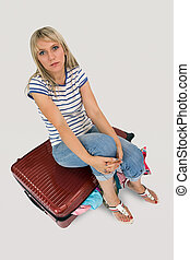 Woman sitting on her luggage