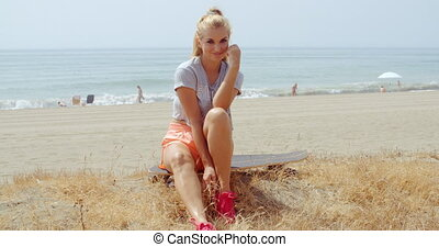 Woman Sitting on her Skateboard at the Beach