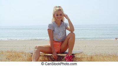 Woman Sitting on her Skateboard on Grassy Ground - Pretty...