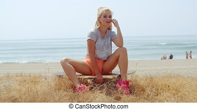 Woman Sitting on her Skateboard on Grassy Ground - Pretty...