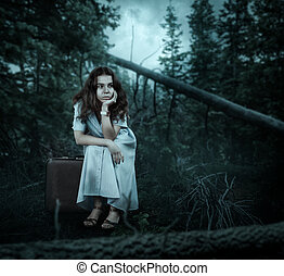 Woman sitting on her suitcase in the forest.