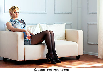 woman sitting on her white sofa in in her flat
