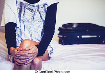 Woman sitting on hotel bed with her suitcase