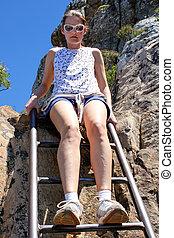 Woman sitting on ladder