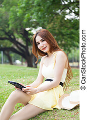 Woman sitting on lawn holding tablet.