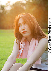 Woman sitting on lawn in park.