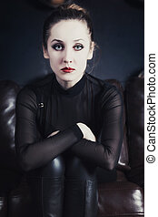 Woman sitting on leather sofa