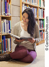 Woman sitting on library floor reading book