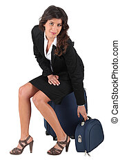 Woman sitting on luggage
