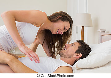 Woman sitting on man in bed
