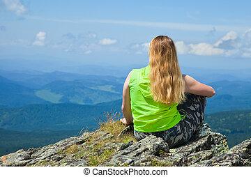 Woman sitting on mountain peak