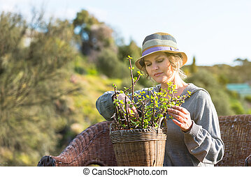 Woman sitting on nature and holding a pot with plant