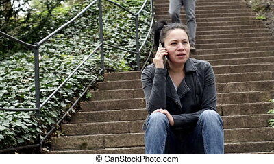 Woman Sitting on Outdoor Stairs on Phone and Man Walks Down the Stairs