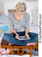 Woman Sitting On Overloaded Suitcase While Using Digital Tablet