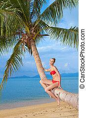 Woman sitting on palm tree