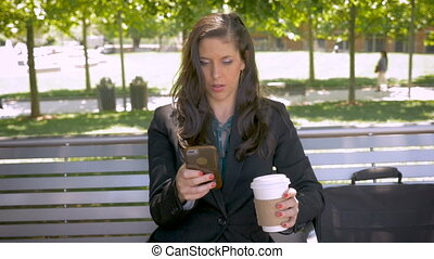 Woman sitting on park bench smiling and drinking coffee on...