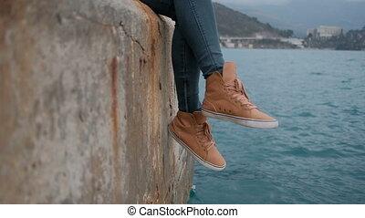 Woman sitting on pier admire picturesque landscape of Montenegro.