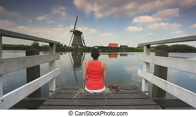woman sitting on pier