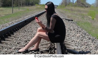 Woman sitting on railway and using