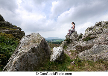 woman sitting on rock