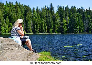 Woman sitting on rock by moraine lake Grosser Arbersee, Germany.