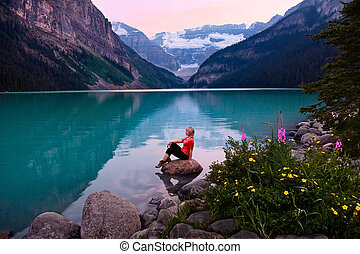Woman sitting on rock in Lake Louise at sunset
