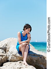 Woman sitting on rocks at the seaside