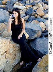 Woman sitting on rocks enjoying italian red wine before party on rocks