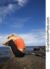 Woman sitting on rocky shore.