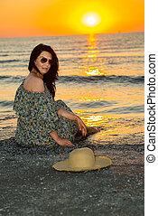 Woman sitting on seashore at sunrise