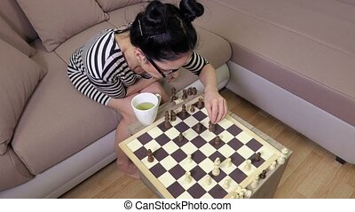 Woman sitting on sofa and playing chess.top view