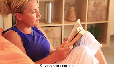 Woman sitting on sofa and reading