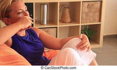 Woman sitting on sofa and smoking
