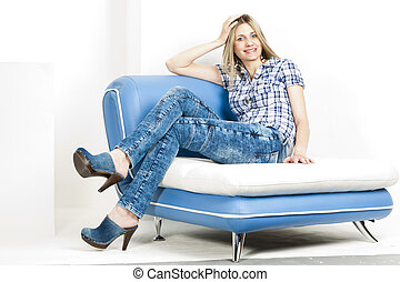 woman sitting on sofa wearing jeans and denim clogs