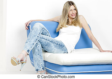 woman sitting on sofa wearing jeans and summer shoes
