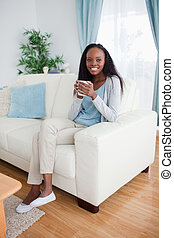 Woman sitting on sofa with a cup