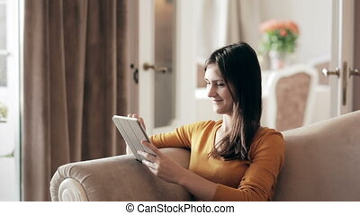 Woman sitting on sofa with touchpad