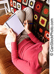 Woman sitting on sofa writing in notebook