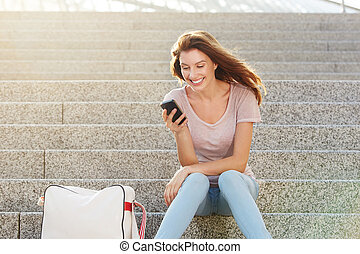 woman sitting on steps and looking at smart phone