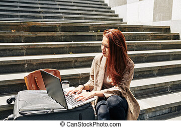 Woman sitting on steps with laptop
