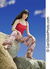 Woman sitting on stone