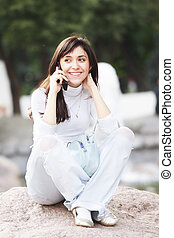 Woman sitting on stone with cellphone